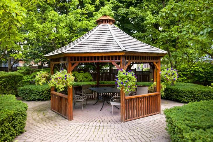 foisor lemn gradina masa verde scaune albe pavele