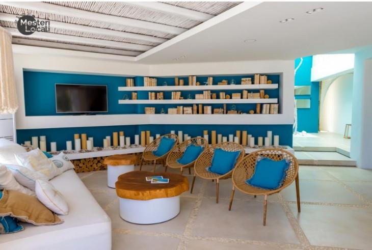 living casa grecia scaune lemn masa lemn perne albastre perete albastru rafturi albe